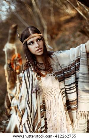 beautiful native indian american woman with warrior shaman make up walking under trees - stock photo