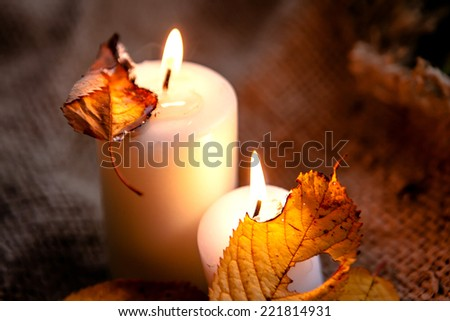 beautiful natural decor for autumnal holiday, old dry maple leaves, pine cones, warm candle light  - stock photo