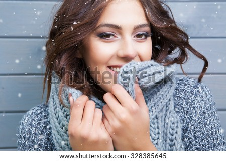 Beautiful natural looking young smiling brunette woman, wearing knitted scarf, covered with snow flakes. Snowing winter beauty concept. - stock photo