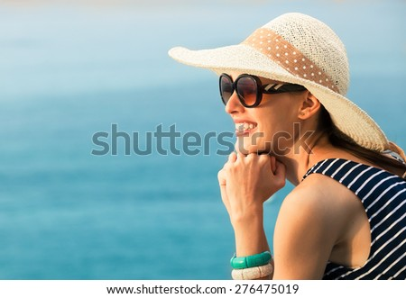 Beautiful natural portrait of woman smiling with blue water background.