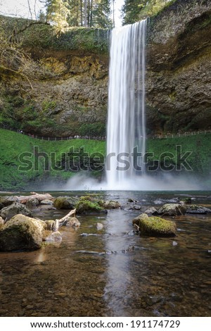 beautiful natural scene of silver lake falls in Oregon with blured people in the path behind them - stock photo