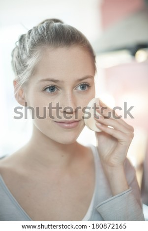 beautiful natural woman applying makeup in front of mirror - stock photo
