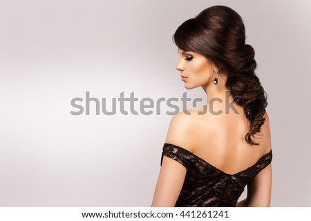Beautiful natural woman with fashion make-up and brunett hair, portrait of an young girl isolated on grey - stock photo