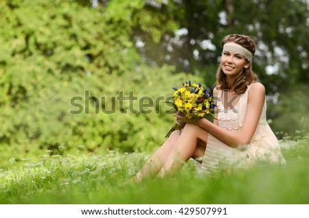 Beautiful natural young blonde smiling  woman on field keep in hand yellow flowers - stock photo