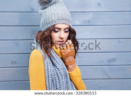 Beautiful natural young brunette woman with eyes closed wearing knitted sweater, leather gloves, scarf and hat. Hair covered with snow flakes. Fall and winter fashion concept. - stock photo