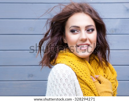 Beautiful natural young smiling brunette woman wearing knitted sweater gloves and scarf. Fall and winter fashion concept. - stock photo