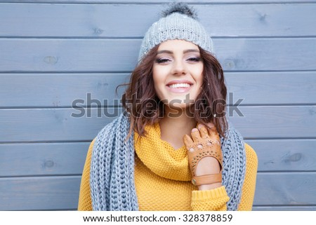 Beautiful natural young smiling brunette woman wearing knitted sweater, leather gloves, scarf and hat. Covered with snow flakes. Fall and winter fashion concept. - stock photo