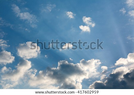 Beautiful nature background blue sky sun rays shine through the clouds - stock photo