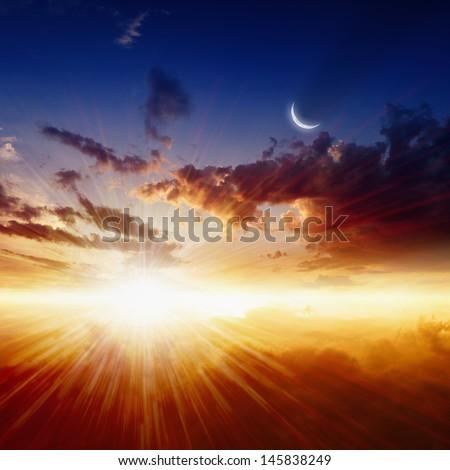 Beautiful nature background - red sunset, bright sun, moon in dark blue sky, glowing horizon - stock photo