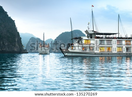 Beautiful nature in Halong bay, Vietnam, Asia. Picturesque scene with blue sky, ripple on water and mountains. Houseboat with lights in dusk. Idea of recreational tourism. Tranquil view of seascape. - stock photo