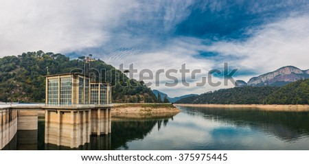 Beautiful nature landscape with dam building in vivid colors. - stock photo