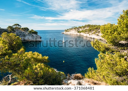 Beautiful nature of Calanques on the azure coast of France. Calanques - a deep bay surrounded by high cliffs. Boat leaves from bay to open sea. - stock photo