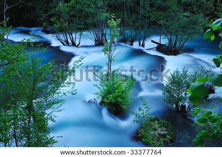 beautiful nature scene with river and waterfall at spring seasson - stock photo