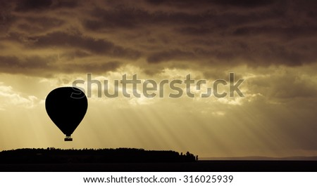 Beautiful nature scene with silhouette of hot air balloon flying at sunset. - stock photo