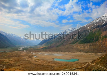 Beautiful nature scenery with bright blue lake in desert valley between two mountain range against the background of cloudy sky in Himalaya, Ladakh, Jammu & Kashmir, Northern India, Central Asia - stock photo