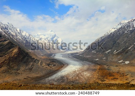 Beautiful nature scenery with melting glacier between two mountain range covered with snow against the background of cloudy sky in Himalaya, Ladakh, Jammu & Kashmir, Northern India, Central Asia - stock photo