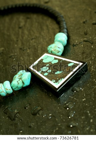 Beautiful necklace from  turquoise on black background - stock photo
