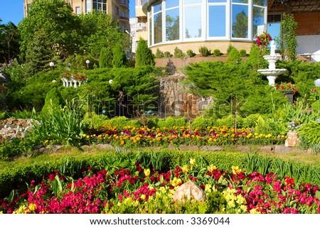 Beautiful neighborhood garden with sculptures, fountains and flowers in sunset. Shot in Ukraine. - stock photo