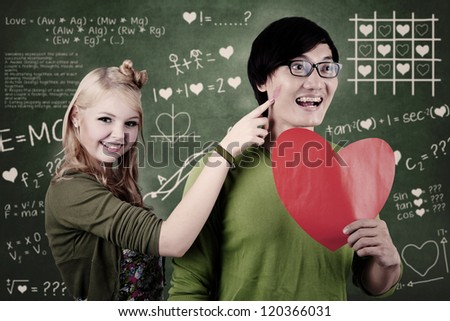 Beautiful nerd girl is teasing her guy whose holding red heart at school - stock photo
