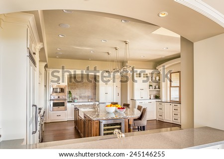 Beautiful New Kitchen with Island, Sink, Cabinets, and Hardwood Floors in New Home - stock photo