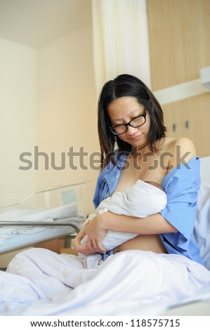 Beautiful new mother happy holding her infant baby and feeding her milk to her baby after giving birth in hospital.