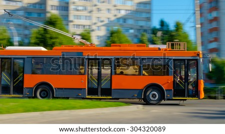 beautiful new orange trolleybus moving early in the morning on the beautiful road - stock photo