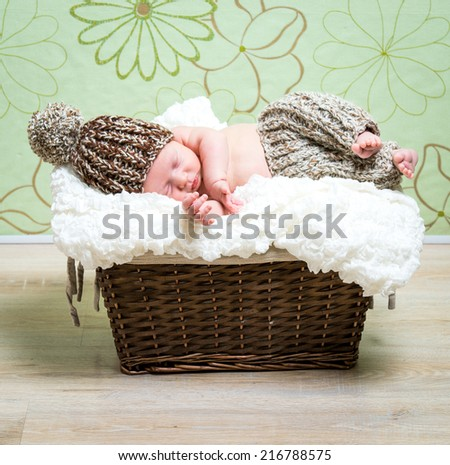 beautiful newborn baby boy asleep in a wicker basket in knitted cap - stock photo
