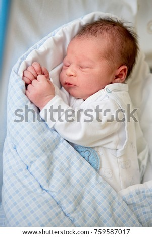 Beautiful newborn baby boy laying in crib in prenatal hospital