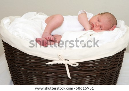 Beautiful newborn baby boy sleeping in a basket - stock photo