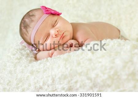 Beautiful newborn baby girl sleeping on a blanket - stock photo