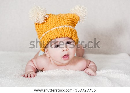Beautiful newborn baby girl with funny yellow hat, lying in her bed and smiling.