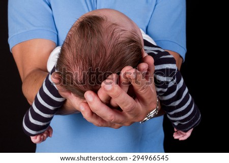 Beautiful newborn baby held by his father - stock photo