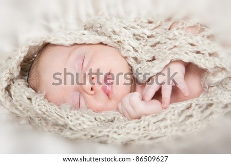 Beautiful newborn baby laying down and sleeping on a soft  background - stock photo