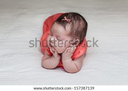 Beautiful newborn baby posing sleeping on her elbows and hands - stock photo