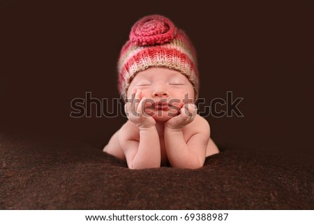 Beautiful newborn baby resting her hands on her face - stock photo