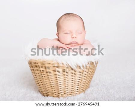 Beautiful newborn baby sleeping in a basket - stock photo
