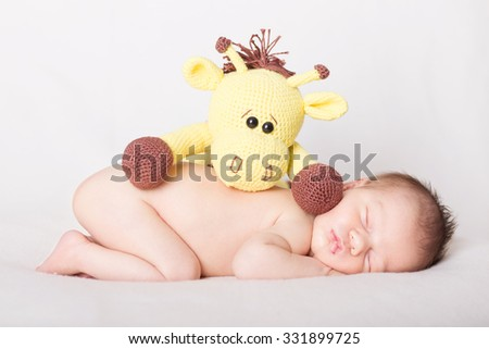 Beautiful newborn baby sleeping on a blanket, protected by a toy - stock photo