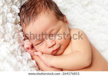 beautiful newborn baby smiles in his sleep - stock photo