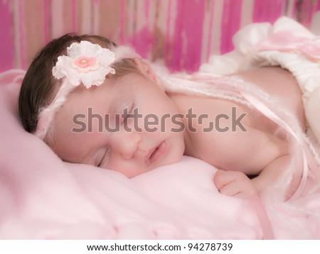 Beautiful newborn girl asleep in her bed with white ruffled bloomers with a pink bow and beautiful headband of yarn and ribbon and a fabric pink flower, - stock photo