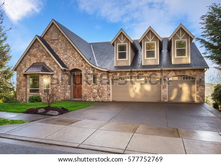 Beautiful, Newly Built Luxury Home Exterior With Stone Facade And Three Car  Garage, And