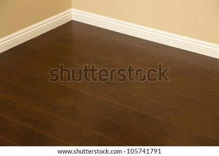 Beautiful Newly Installed Brown Laminate Flooring and Baseboards in Home. - stock photo
