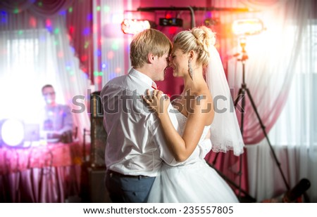 Beautiful newly married couple dancing at colorful lights and flares - stock photo