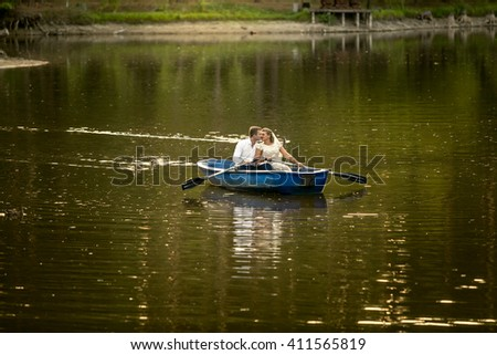 Beautiful newly married couple kissing on rowing boat in the middle of lake - stock photo