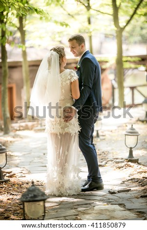 Beautiful newly married couple walking at sunny park - stock photo