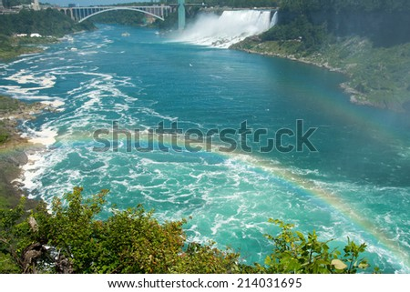Beautiful Niagara Falls with rainbow. Niagara Falls is the collective name for three waterfalls that straddle the international border between Canada and the United States. - stock photo