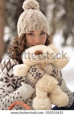 Beautiful,nice,smiling,little,attractive,wearing sweater,hut,mittens,girl with a fluffy,soft,beige,white,teddy bear,cute toy,curly,light hair in snow,winter,frosty forest,sweet bear,tiny bear,petite - stock photo