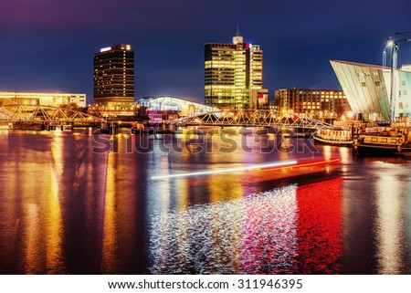 Beautiful night in Amsterdam. Night illumination of buildings and boats near the water in the canal.  - stock photo
