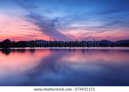 Beautiful night landscape on the mountain lake with stars and reflected clouds in water in spring. Colorful sky.  Nature background  - stock photo