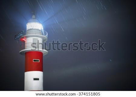 Beautiful night shot of a lighthouse with star trails in the background in Punta de Teno, Tenerife, Canary island,  Spain.  - stock photo