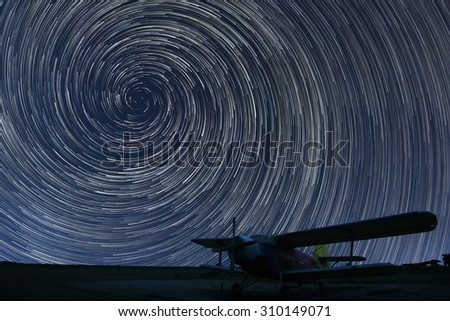 Beautiful night sky, Spiral Star trails over small airport lonely airplane. Vortex Star trails. - stock photo